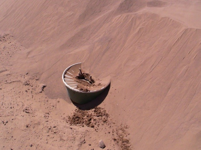 A Groasis Waterboxx almost covered entirely with sand in the Sahara Desert in Mexico